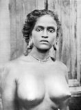Woman of the Tiyan caste in Malabar, where the females of many castes wear no clothing above the waist. Metal discs or rolls of palm-leaf are inserted in the lobes of the ears, which are dilated during infancy. The tali (marriage badge) and metal talismans are suspended from a necklace round the neck.