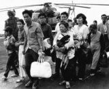 CAMP FOSTER, OKINAWA, Japan ・South Vietnamese refugees walk across a U.S. Navy vessel. Operation Frequent Wind, the final operation in Saigon, began April 29, 1975. During a nearly constant barrage of explosions, the Marines loaded American and Vietnamese civilians, who feared for their lives, onto helicopters that brought them to waiting aircraft carriers. The Navy vessels brought them to the Philippines and eventually to Camp Pendleton, Calif. (Official U.S. Navy photo in Public Domain).